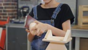 Enfants dans la fabrication de menuiserie Fille dans son 10s fonctionnant avec un tissu abrasif et un bois Plan rapproché de peti banque de vidéos