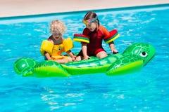 Enfants dans la piscine avec le jouet gonflable Image libre de droits
