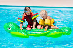 Enfants dans la piscine avec le jouet gonflable Photographie stock