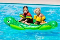 Enfants dans la piscine avec le jouet gonflable Photo stock