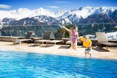 Enfants dans la piscine extérieure de la station de vacances alpine Photos stock