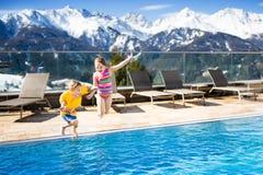 Enfants dans la piscine extérieure de la station de vacances alpine Image libre de droits