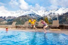 Enfants dans la piscine extérieure de la station de vacances alpine Photographie stock libre de droits