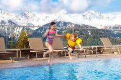 Enfants dans la piscine extérieure de la station de vacances alpine Images libres de droits
