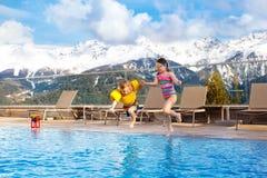 Enfants dans la piscine extérieure de la station de vacances alpine Photo stock