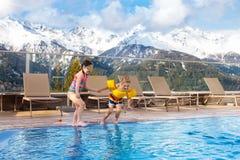 Enfants dans la piscine extérieure de la station de vacances alpine Images stock