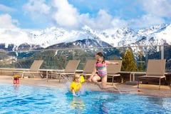 Enfants dans la piscine extérieure de la station de vacances alpine Photographie stock