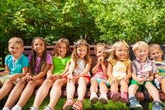 Enfants dans la rangée sur le banc, parc d'été Photos libres de droits