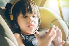 Enfants dans la voiture avec des écouteurs regardant le smartphone de la lumière du soleil Images libres de droits