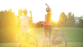 Enfants dans le casque sur le salut de Soleil Levant de bicyclette en parc d'été banque de vidéos