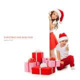 Enfants dans le chapeau de Santa jetant un coup d'oeil par derrière le panneau d'affichage vide de signe Images stock