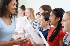 Enfants dans le choeur d'école encouragé par le professeur image stock