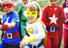 Enfants dans le costume de super héros jouant ensemble Images stock