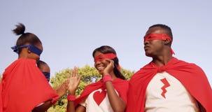 Enfants dans le costume des super héros battant leurs mains de leurs parents banque de vidéos