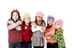 Enfants dans le froid de tremblement de chapeaux d'hiver Images stock
