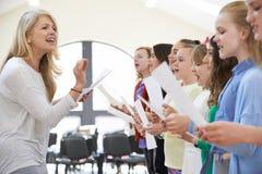 Enfants dans le groupe chanteur encouragé par le professeur Photo libre de droits