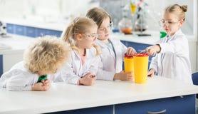 Enfants dans le laboratoire de science faisant l'expérience image stock