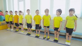 Enfants dans le support jaune dans la ligne à la leçon de pinte dans l'école maternelle banque de vidéos