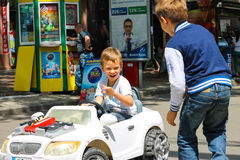 Enfants dans le terrain de jeux montant une voiture de jouet Nikolaev, Ukraine Photographie stock libre de droits