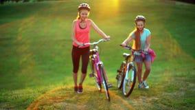 Enfants dans le vélo supérieur de promenade de colline de casque de bicyclette banque de vidéos