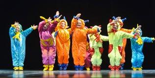 Enfants dans les étrangers colorés drôles de combinaisons dansant sur l'étape Images stock