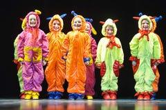 Enfants dans les étrangers colorés drôles de combinaisons dansant sur l'étape Photos libres de droits