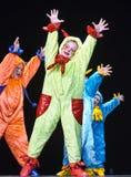 Enfants dans les étrangers colorés drôles de combinaisons dansant sur l'étape Photo stock
