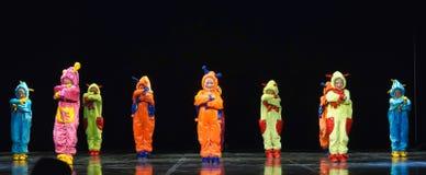 Enfants dans les étrangers colorés drôles de combinaisons dansant sur l'étape Image libre de droits