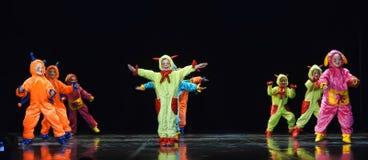 Enfants dans les étrangers colorés drôles de combinaisons dansant sur l'étape Photographie stock