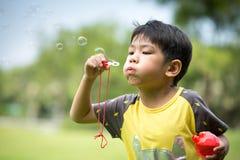 Enfants dans les bulles de savon de soufflement de parc Images libres de droits