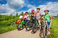 Enfants dans les casques de port de rangée tenant des vélos Images libres de droits