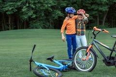 Enfants dans les casques embrassant tout en tenant les bicyclettes proches au parc Photos libres de droits