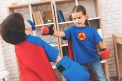Enfants dans les costumes rouges et bleus des super héros Ils dans les masques Enfants posant dans la chambre lumineuse Photographie stock