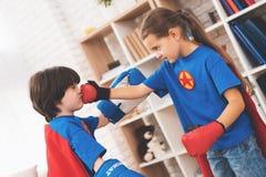 Enfants dans les costumes rouges et bleus des super héros Ils dans les masques Enfants posant dans la chambre lumineuse Image libre de droits