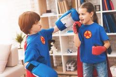 Enfants dans les costumes rouges et bleus des super héros Ils dans les masques Enfants posant dans la chambre lumineuse Photos stock