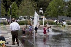 Enfants dans une fontaine et des parents les observant Image stock