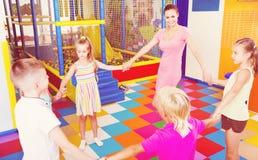 Enfants dansant avec le professeur dans la classe d'école Photographie stock
