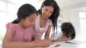 Enfants de aide de mère avec des devoirs banque de vidéos