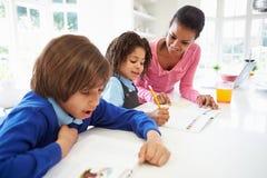 Enfants de aide de mère avec des devoirs dans la cuisine photos libres de droits