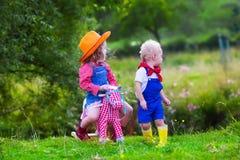 Enfants de cowboy jouant avec le cheval de jouet Photographie stock libre de droits