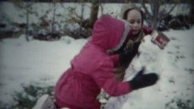 enfants (de film de 8mm) construisant le bonhomme de neige 1955 banque de vidéos