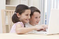 Enfants de garçon et de fille à l'aide de l'ordinateur portable à la maison Photo stock