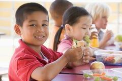 Enfants de jardin d'enfants mangeant le déjeuner Photos stock