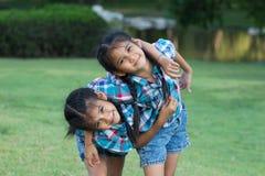 Enfants de jumeaux jouant en parc Images libres de droits