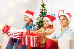 Enfants de l'adolescence avec des présents sur la partie de soirée du Nouveau an Photos stock