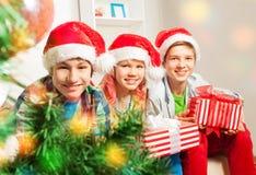 Enfants de l'adolescence mignons avec des présents par l'arbre de Noël Photos libres de droits
