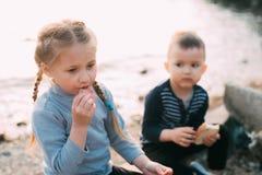 Enfants de la fille de mer mangeant le garçon de saucisse et de pain image stock