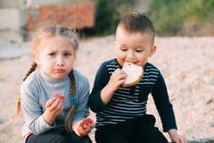 Enfants de la fille de mer mangeant le gar?on de saucisse et de pain photo libre de droits