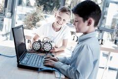 Enfants de la préadolescence futés travaillant sur le programme pour leur machine robotique Image stock