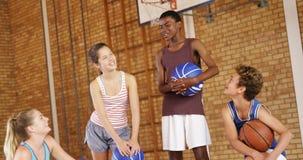 Enfants de lycée agissant l'un sur l'autre les uns avec les autres au terrain de basket banque de vidéos